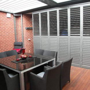 Medium sized classic patio in Other with decking and an awning.