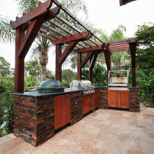 Inspiration for a huge tropical backyard stone patio kitchen remodel in Tampa with a pergola