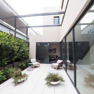 Inspiration for a mid-sized contemporary courtyard patio in Melbourne with no cover and tile.