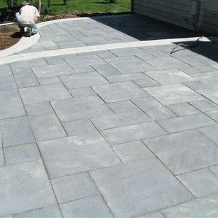 Mid-sized minimalist backyard stone patio photo in Milwaukee with no cover
