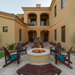 Esempio di un patio o portico mediterraneo di medie dimensioni e in cortile con un focolare, piastrelle e nessuna copertura