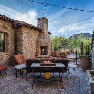 Foto di un ampio patio o portico mediterraneo nel cortile laterale con pavimentazioni in mattoni e nessuna copertura