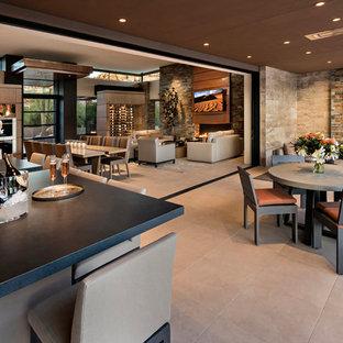 Immagine di un grande patio o portico american style con piastrelle, un tetto a sbalzo e un caminetto
