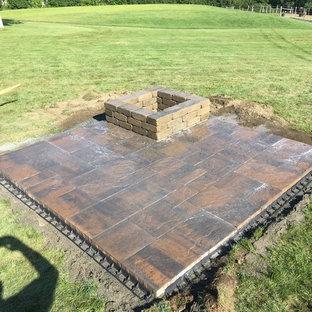 Foto di un piccolo patio o portico country dietro casa con un focolare e lastre di cemento