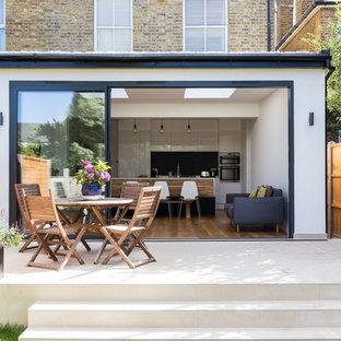 Ispirazione per un patio o portico design di medie dimensioni e dietro casa con piastrelle