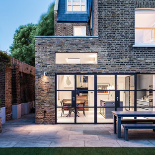 Contemporary back patio in London with concrete paving and no cover.