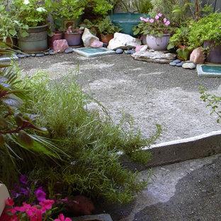 Immagine di un piccolo patio o portico eclettico dietro casa con un giardino in vaso, lastre di cemento e un parasole