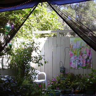 Design ideas for a small eclectic back patio in Los Angeles with a potted garden, concrete slabs and an awning.