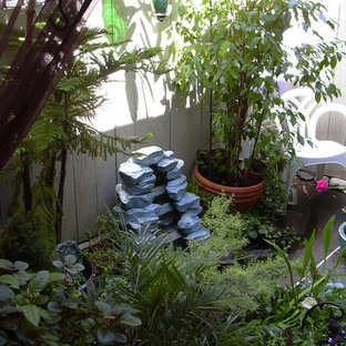 Photo of a small bohemian back patio in Los Angeles with a potted garden, concrete slabs and an awning.