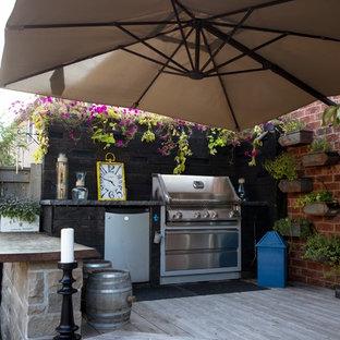 Immagine di un patio o portico stile americano di medie dimensioni e dietro casa con pedane e un parasole