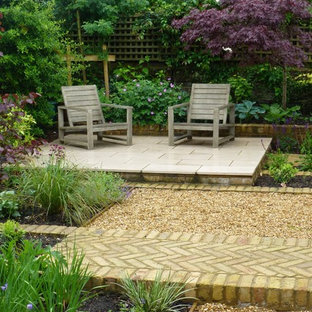 This is an example of a small classic back patio in London with natural stone paving.
