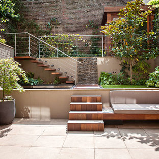 This is an example of a small contemporary back patio in London with concrete paving and no cover.