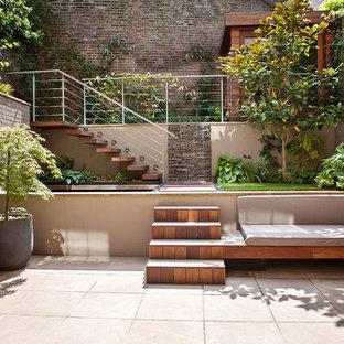 Foto de patio contemporáneo, pequeño, sin cubierta, en patio trasero, con adoquines de hormigón y chimenea