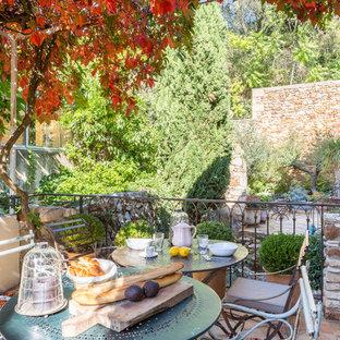 Cette image montre une terrasse avec des plantes en pots méditerranéenne de taille moyenne avec aucune couverture et du carrelage.