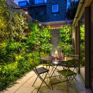 Ejemplo de patio actual, pequeño, en patio trasero, con jardín vertical y adoquines de piedra natural