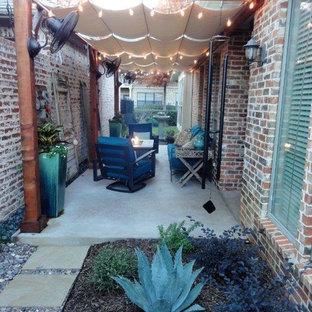 Esempio di un piccolo patio o portico classico nel cortile laterale con un focolare, pavimentazioni in cemento e un parasole