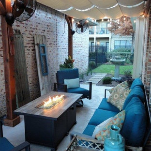 Inspiration for a small traditional side patio in Dallas with a fire feature, concrete paving and an awning.