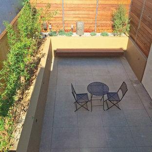 Пример оригинального дизайна: маленький дворик на заднем дворе в средиземноморском стиле с мощением тротуарной плиткой