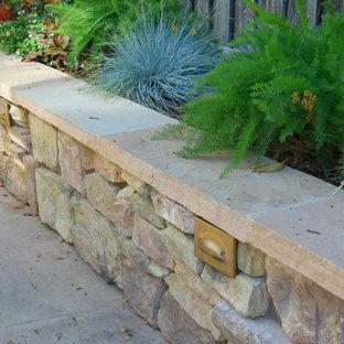 Inspiration pour une terrasse arrière traditionnelle avec des pavés en pierre naturelle et une pergola.