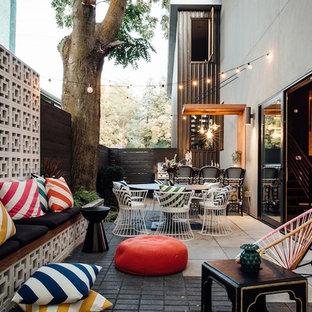 Foto di un patio o portico eclettico di medie dimensioni e dietro casa con pavimentazioni in mattoni e un parasole