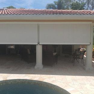 Foto di un patio o portico tropicale di medie dimensioni e dietro casa con piastrelle e un tetto a sbalzo