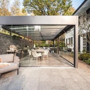 Großer Moderner Patio hinter dem Haus mit Outdoor-Küche, Betonplatten und Gazebo in Hamburg