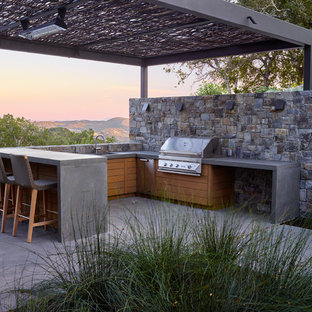 This is an example of a contemporary patio in San Francisco with an outdoor kitchen, concrete slabs and a gazebo.