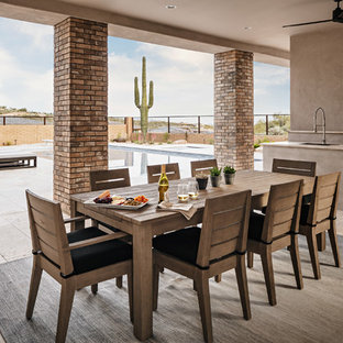 Patio kitchen - large contemporary backyard stone patio kitchen idea in Phoenix with a roof extension