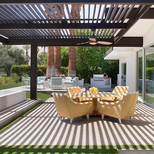 Aménagement d'une grande terrasse arrière rétro avec une pergola, un foyer extérieur et une dalle de béton.