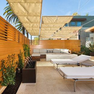 Ejemplo de patio moderno, de tamaño medio, con fuente, suelo de baldosas y toldo