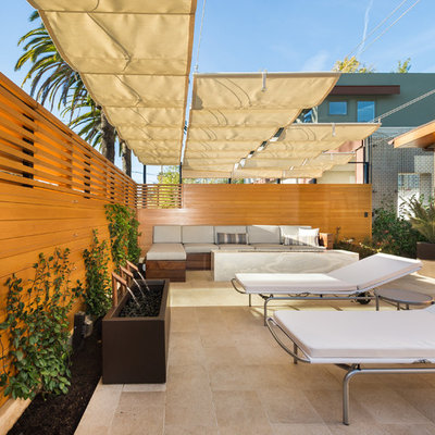 Inspiration for a mid-sized modern tile patio fountain remodel in Los Angeles with an awning