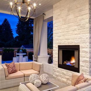 Idee per un patio o portico tradizionale con piastrelle, un tetto a sbalzo e un caminetto
