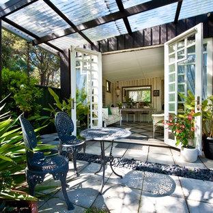 Esempio di un patio o portico eclettico di medie dimensioni e dietro casa con cemento stampato e una pergola