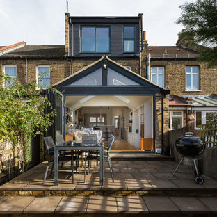 This is an example of a medium sized traditional back patio in London with no cover.