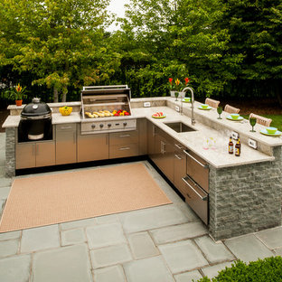 Photo of a large classic back patio in New York with an outdoor kitchen, an awning and concrete paving.