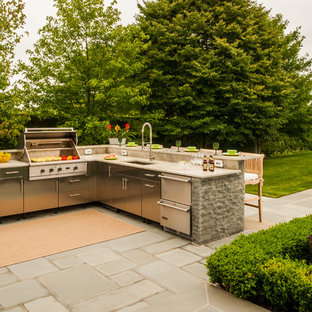 Patio kitchen - large traditional backyard concrete paver patio kitchen idea in New York with an awning