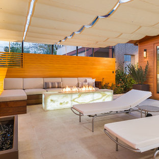 Inspiration for a mid-sized contemporary tile patio remodel in Los Angeles with a fire pit and an awning