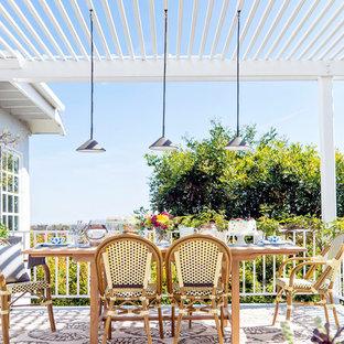 Foto di un piccolo patio o portico eclettico dietro casa con lastre di cemento e una pergola