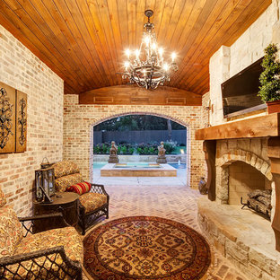 This is an example of a large traditional backyard patio in Dallas with brick pavers and a roof extension.
