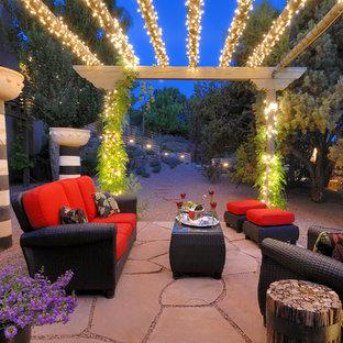 Idée de décoration pour une terrasse arrière sud-ouest américain de taille moyenne avec des pavés en pierre naturelle et une pergola.