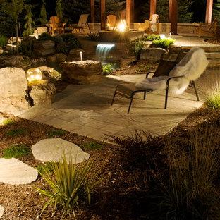 Immagine di un grande patio o portico etnico dietro casa con fontane, pavimentazioni in cemento e una pergola