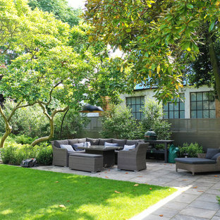 Inspiration for a classic back patio in London with tiled flooring and no cover.