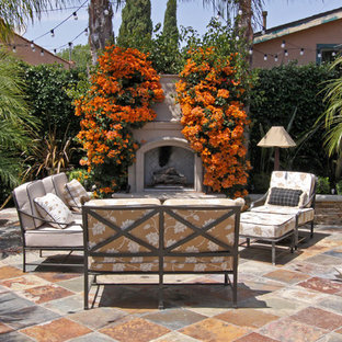 Patio - mediterranean courtyard patio idea in Orange County with a fire pit