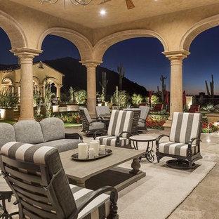 Immagine di un ampio patio o portico mediterraneo dietro casa con pavimentazioni in pietra naturale e un gazebo o capanno