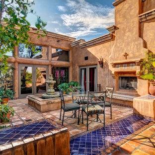 Foto di un grande patio o portico american style in cortile con piastrelle, nessuna copertura e un caminetto