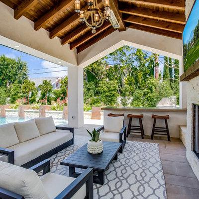 Patio - mediterranean patio idea in Orange County with a roof extension