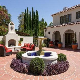 Immagine di un grande patio o portico dietro casa con un focolare, piastrelle e nessuna copertura