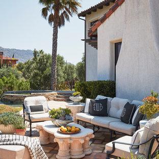 Esempio di un ampio patio o portico mediterraneo dietro casa con fontane, nessuna copertura e piastrelle