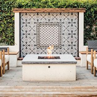 Imagen de patio mediterráneo, sin cubierta, en patio trasero, con brasero y entablado