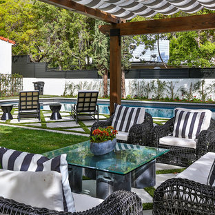 This is an example of a large mediterranean back patio in Los Angeles with an awning.